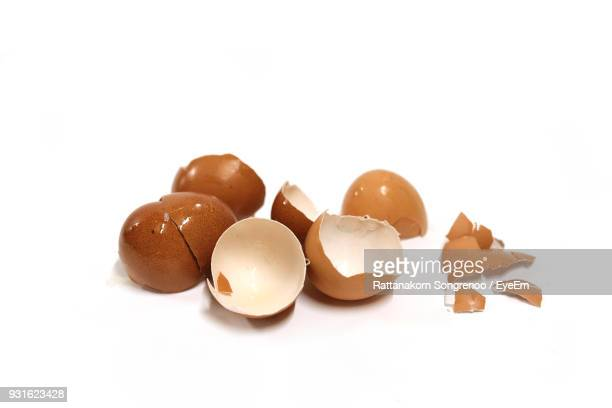 Close-Up Of Broken Eggshells Over White Background