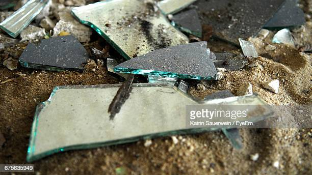 Close-Up Of Broken Glass Pieces On Sand