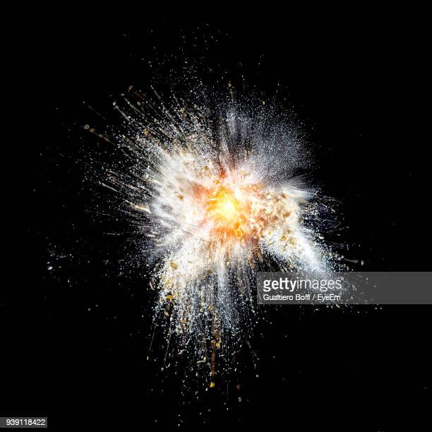 close-up of broken light bulb against black background - exploding glass stock photos and pictures