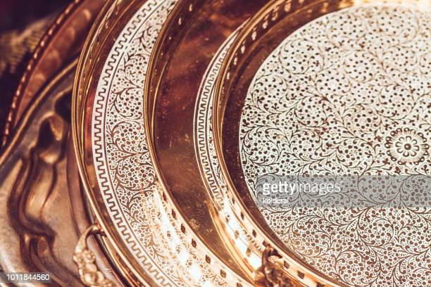 Close-up of bronze engraved Arabic style trays
