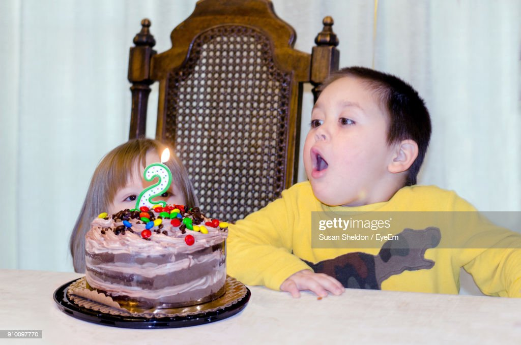 Closeup Of Brother And Sister Looking At Birthday Cake On Table