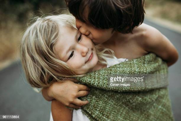 close-up of brother kissing sister while standing on country road - nur kinder stock-fotos und bilder
