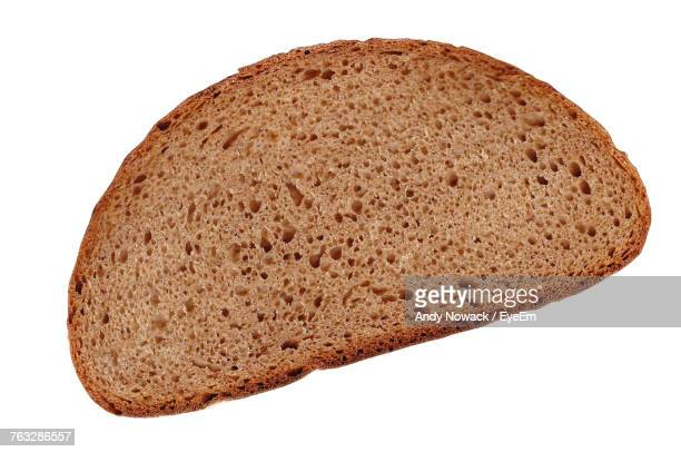 close-up of brown bread over white background - brot stock-fotos und bilder