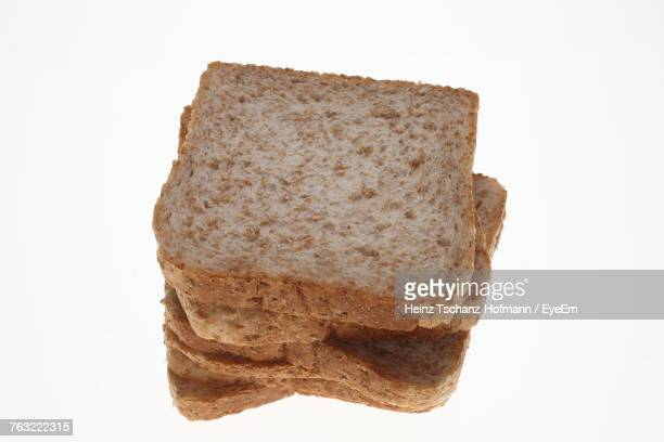 Close-Up Of Brown Breads Stacked Against White Background