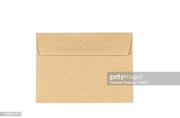 close-up of brown envelope over white background - envelope stock pictures, royalty-free photos & images