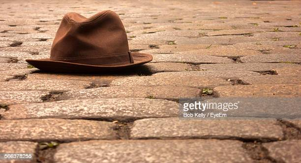 close-up of brown fedora hat on cobblestone street - fedora stock pictures, royalty-free photos & images
