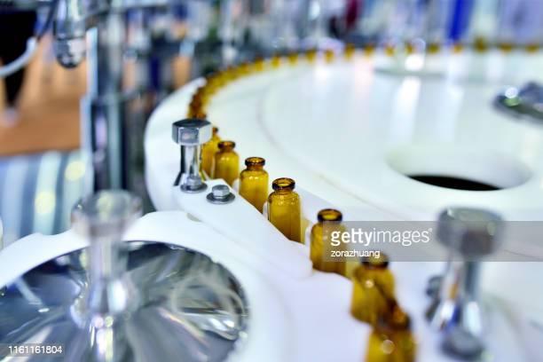 close-up van bruine glazen fles op draaitafel productielijn - chemische stof stockfoto's en -beelden