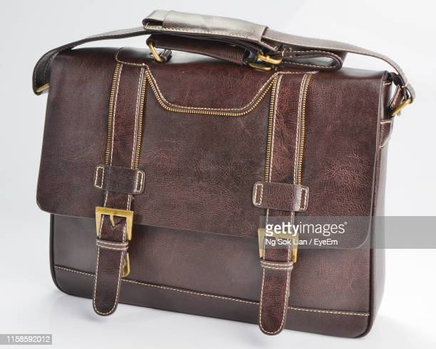 close-up of brown leather bag over white background - brown belt stock pictures, royalty-free photos & images