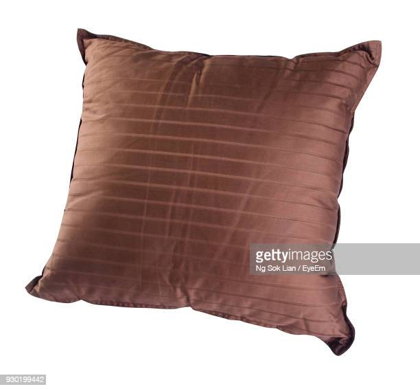close-up of brown pillow over white background - cushion stock photos and pictures