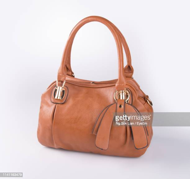 close-up of brown purse against white background - brown purse stock pictures, royalty-free photos & images