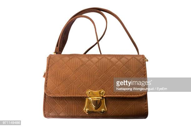 close-up of brown purse over white background - brown purse stock pictures, royalty-free photos & images