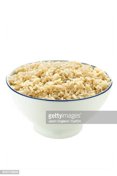 Close-Up Of Brown Rice Over White Background
