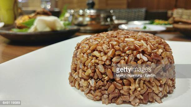 Close-Up Of Brown Rice Served In Plate On Table