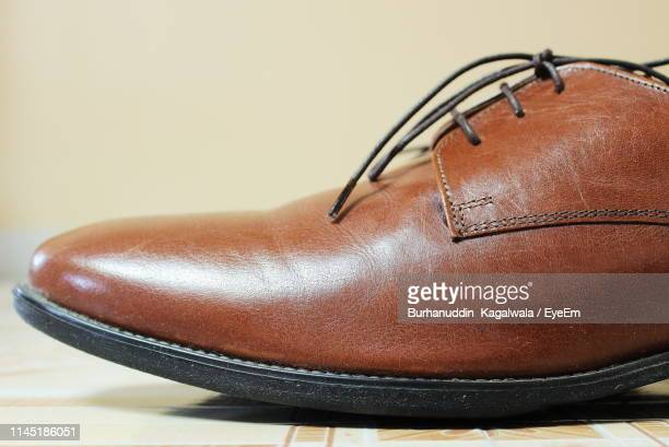 close-up of brown shoe on table - leather shoe stock pictures, royalty-free photos & images