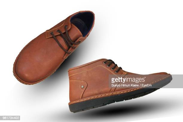 close-up of brown shoes levitating against white background - brown shoe stock photos and pictures