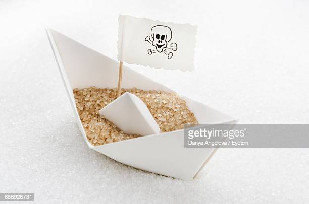 Close-Up Of Brown Sugar And Danger Sign In Paper Boat