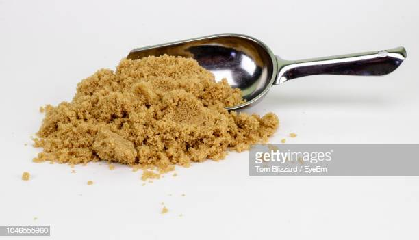 Close-Up Of Brown Sugar And Spoon On White Background