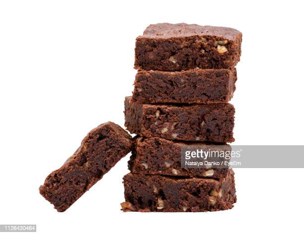 close-up of brownies stack against white background - brownie stock pictures, royalty-free photos & images
