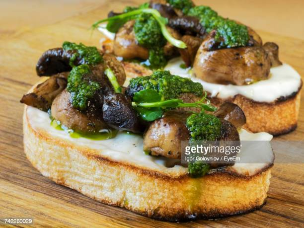 Close-Up Of Bruschetta Served With Champignons And Spinach On Cutting Board