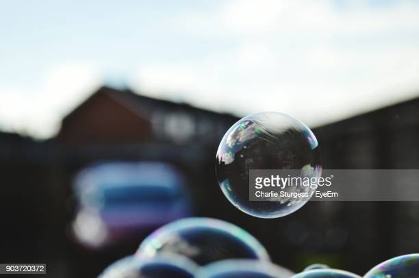 Close-Up Of Bubbles With House And Car In Background