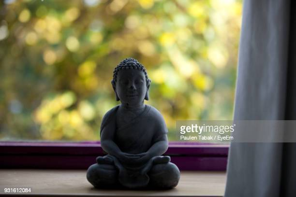 close-up of buddha statue on widow sill - paulien tabak stock pictures, royalty-free photos & images