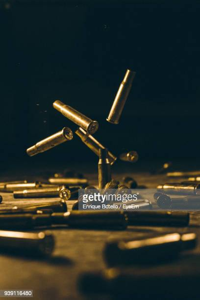 close-up of bullet shells on table against black background - bullet stock photos and pictures