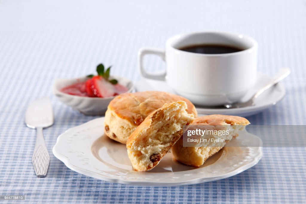 Close-Up Of Buns With Coffee Cup And Strawberries In Plate On Table : Stock Photo