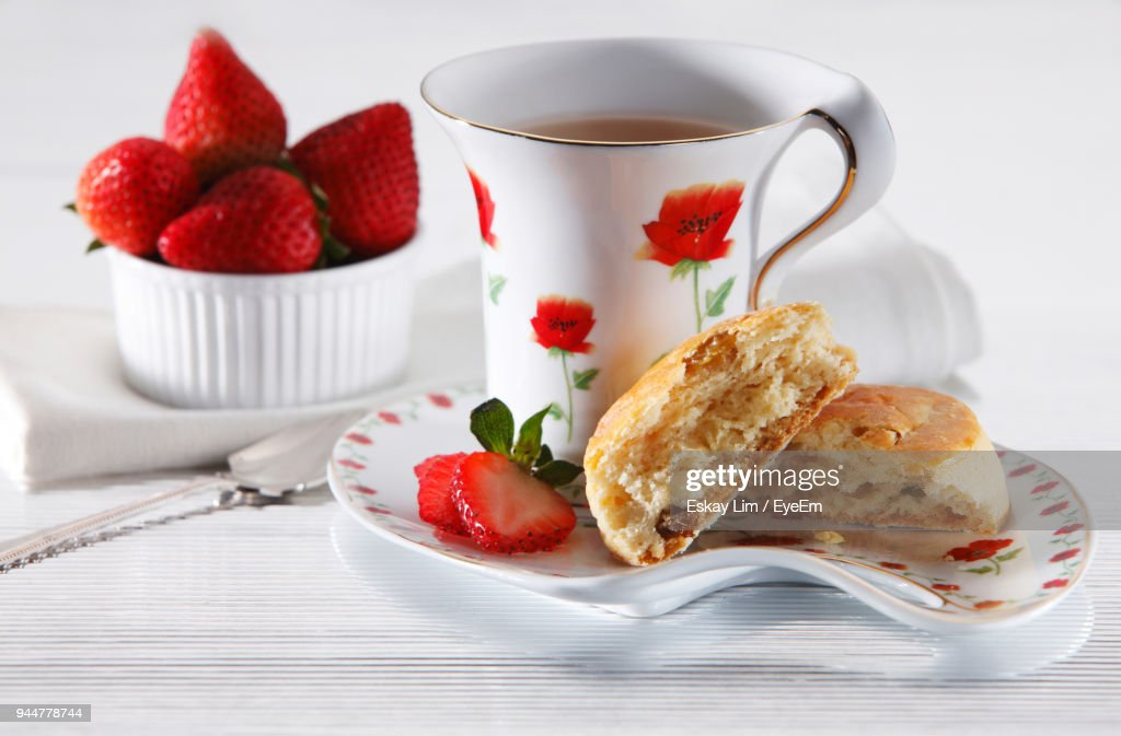 Close-Up Of Buns With Tea Mug And Strawberries In Plate On Table : Stock Photo