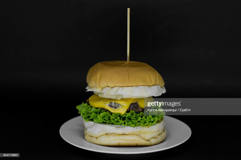 Close-Up Of Burger Against Black Background : Stock Photo