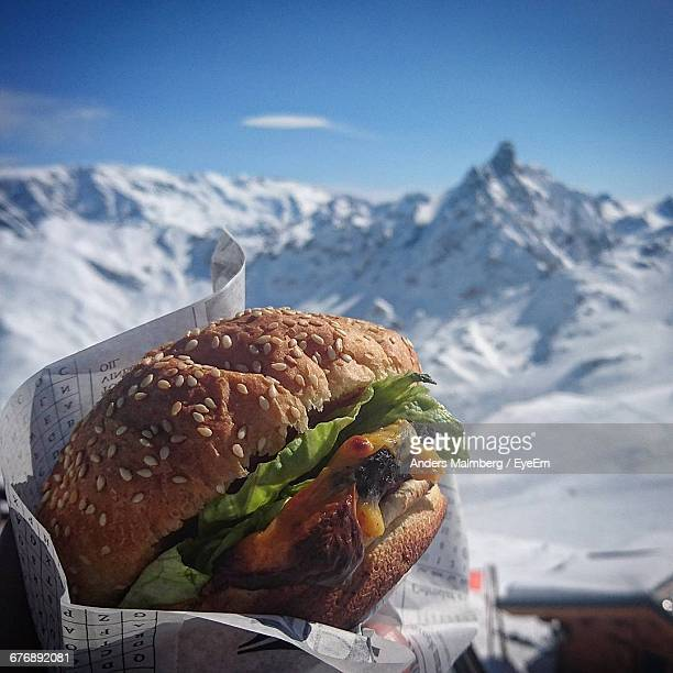 Close-Up Of Burger Against Snowcapped Mountain