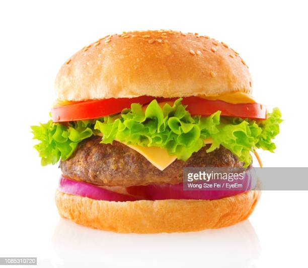 close-up of burger against white background - burger stock pictures, royalty-free photos & images