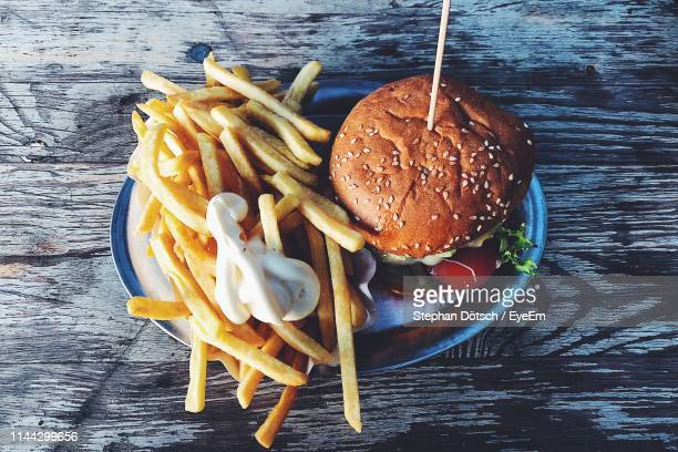 close-up of burger and french fries in bowl on table - fast food french fries stock pictures, royalty-free photos & images