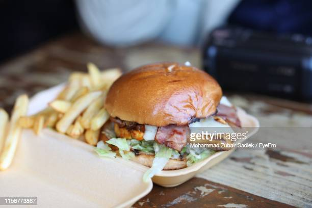 close-up of burger on table - unhealthy eating stock pictures, royalty-free photos & images