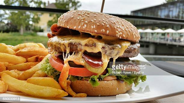 close-up of burger with french fires served in restaurant - cheeseburger stock pictures, royalty-free photos & images