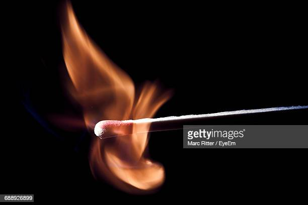 close-up of burning candle against black background - fiammifero foto e immagini stock