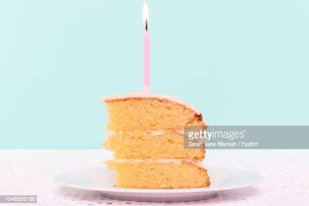 Close-Up Of Burning Candle In Cake On Table