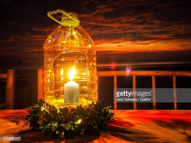 Close-Up Of Burning Candle In Plastic Bottle On Table Against Sky During Sunset