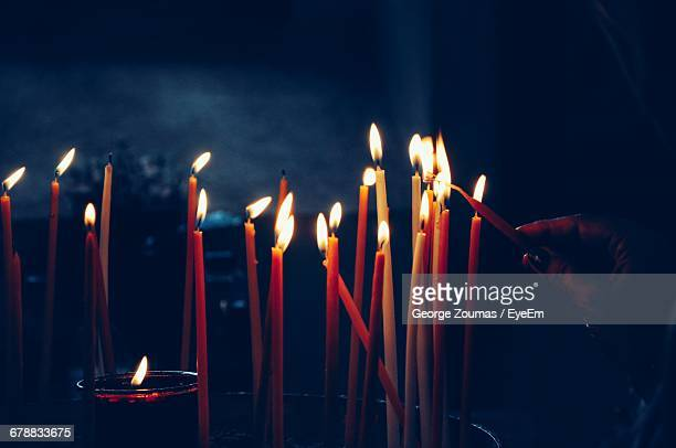 close-up of burning candles in the darkness - cero foto e immagini stock