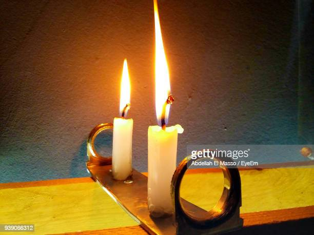 Close-Up Of Burning Candles On Table At Home