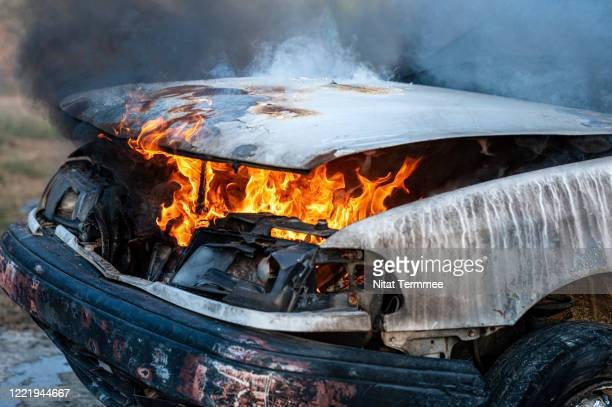 close-up of burning car engine after a frontal crash collision on the roadside with flame and smoke. - terrorisme photos et images de collection