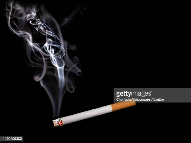 close-up of burning cigarette against black background - cigarette stock pictures, royalty-free photos & images