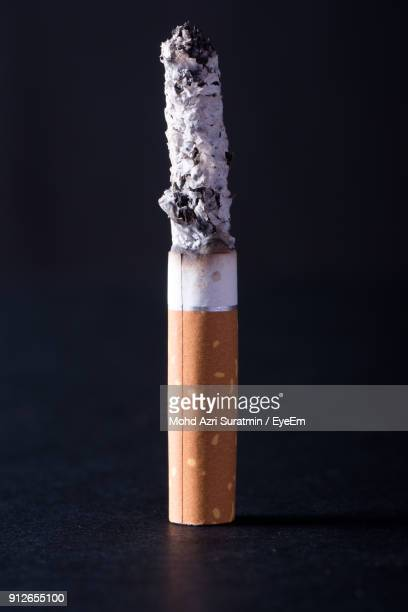 close-up of burning cigarette against black background - ash stock pictures, royalty-free photos & images