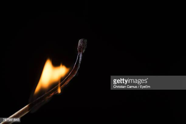Close-Up Of Burning Matchstick Against Black Background