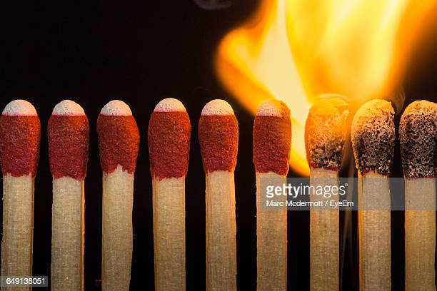 close-up of burning matchsticks against black background - fiammifero foto e immagini stock