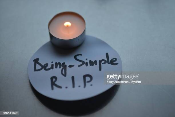 close-up of burning tea light candle with text on paper at table - rest in peace stock pictures, royalty-free photos & images