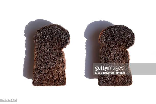Close-Up Of Burnt Toasted Breads On White Background