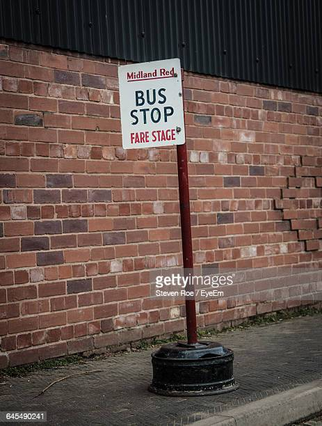 Close-Up Of Bus Stop Sign Against Brick Wall
