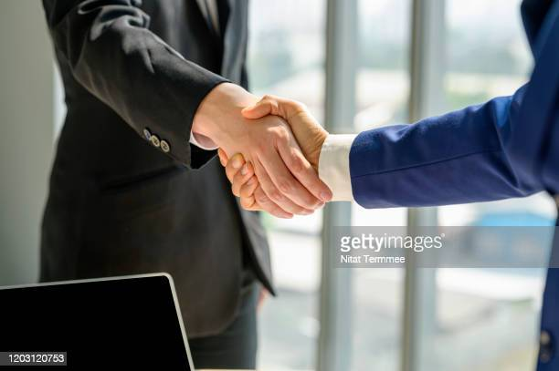 close-up of business handshake deal success concept. - handshake stock pictures, royalty-free photos & images