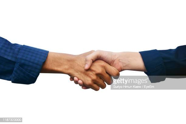 close-up of business people shaking hands against white background - handshake stock pictures, royalty-free photos & images