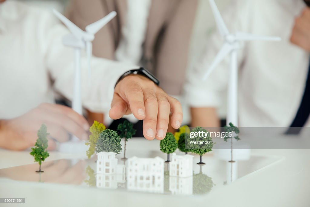 Close-up of business people wind turbine model and houses on conference table : Stock-Foto